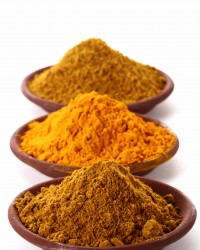 piles of bright Curry Powder and tumeric in teracotta dish